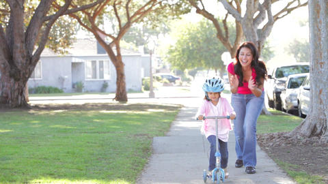 Mother Teaching Daughter To Ride Scooter Footage