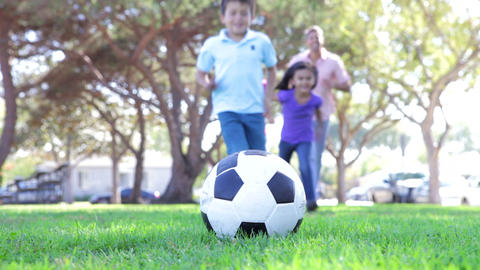 Family Running Towards Soccer Ball And Kicking It Footage