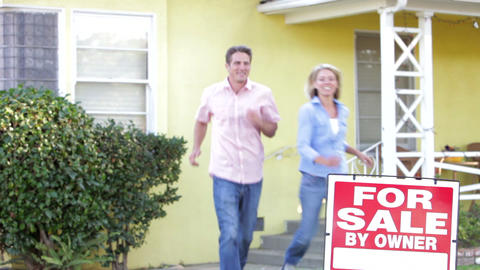 Couple Standing By For Sale Sign Outside Home stock footage