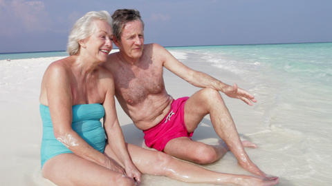 Senior Couple Sitting On Beautiful Beach Footage