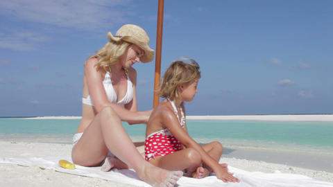 Mother Protecting Daughter With Sun Lotion On Beac ビデオ