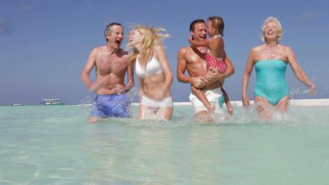 Multi Generation Family Having Fun In Sea On Beach Footage