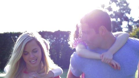 Parents Giving Children Piggyback Rides In Garden Footage
