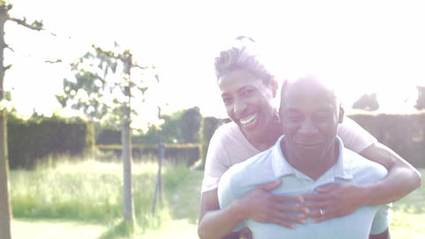 Mature Man Giving Woman Piggyback In Countryside Footage