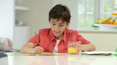 Hispanic Boy Doing Homework On Kitchen Counter Footage
