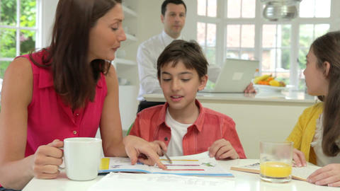 Mother Helping Children With Homework As Father Us stock footage