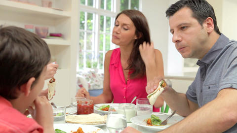 Hispanic Family Sitting At Table Eating Meal Toget Footage