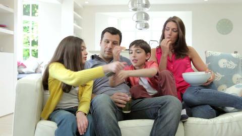 Hispanic Family Sitting On Sofa Watching TV Togeth Footage