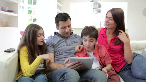 Hispanic Family Sitting On Sofa With Digital Table Footage
