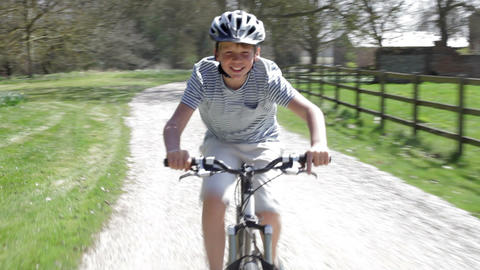 Young Boy Riding Bike Along Country Track stock footage