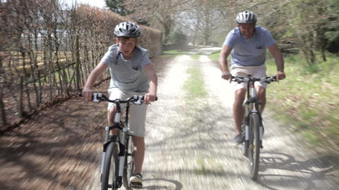 Father And Son Riding Bikes Along Country Track Footage