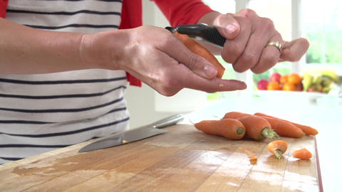 Close Up Of Woman Peeling Carrots On Wooden Board Footage