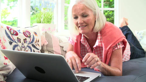 Middle Aged Woman Using Laptop Lying On Sofa Live Action