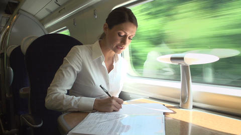 Female Commuter On Train Working On Document Footage