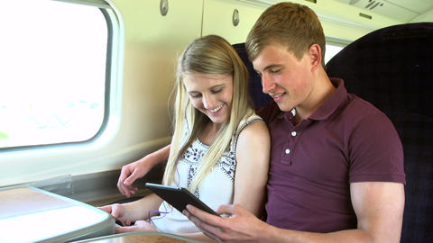 Young Couple Reading E Book On Train Journey stock footage