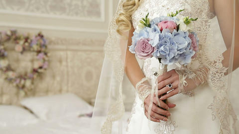 wedding bouquet in bride hands against background of wreath in shape of heart Footage