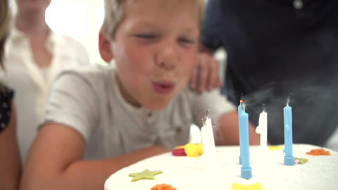 Slow Motion Sequence Of Boy Blowing Out Candles On Footage