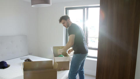 Man Moving Into New Home Unpacking Clothes In Bedr Footage