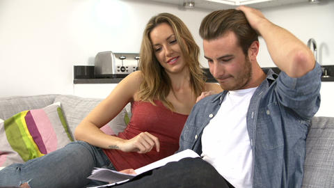 Young Couple Looking Through Personal Finances At  Footage
