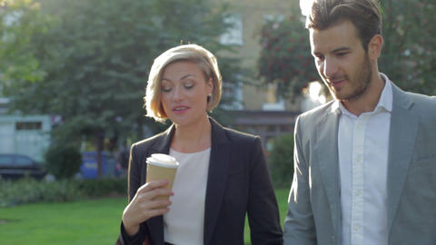 Business Couple Walking Through Park With Takeaway Footage