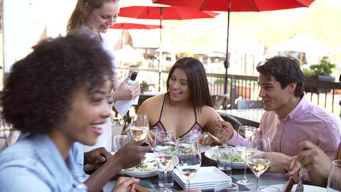 Waitress Pouring Wine For Group Of Friends At Rest Footage