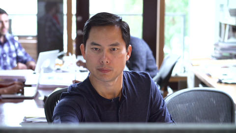 Architect Working At Desk With Meeting In Backgrou Footage