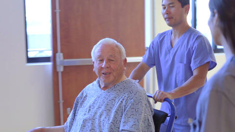 Senior Male Patient Being Pushed In Wheelchair By  Footage