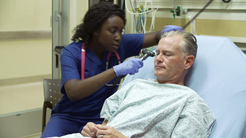 Nurse Examining Mature Male Patient In Hospital Be stock footage