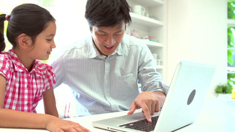 Asian Father Helping Daughter To Use Laptop At Hom Footage