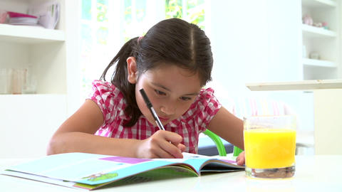 Young Asian Girl Doing Homework Seated At Table stock footage
