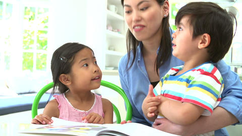 Asian Mother Reading A Story To Children Stock Video Footage