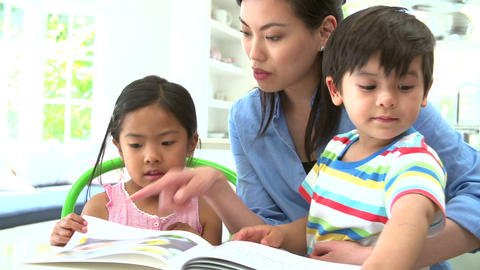 Asian Mother Reading A Story To Children Footage