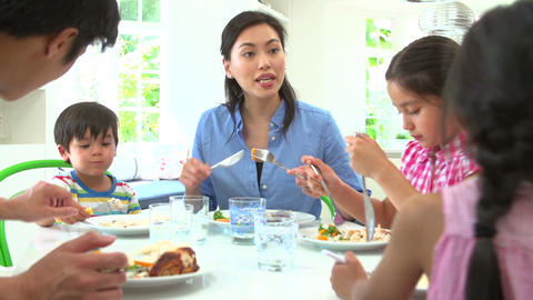 Asian Family Sitting At Table Eating Meal Together Footage