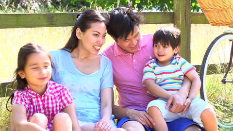 Asian Family Resting By Fence With Old Fashioned C Footage