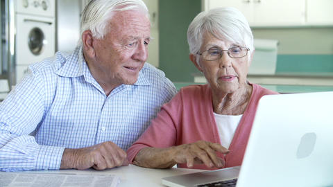 Senior Couple Using Laptop At Home In Kitchen stock footage