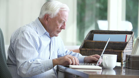 Senior Man Using Laptop On Desk At Home stock footage