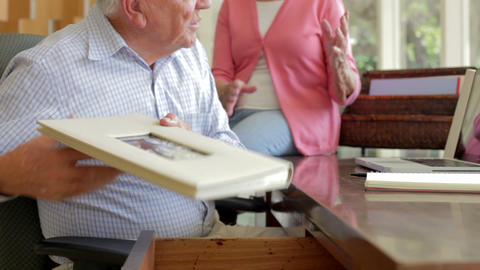 Senior Couple Looking At Picture In Frame And Phot Footage