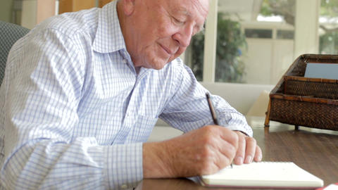 Senior Man Writing Memoirs In Book Sitting At Desk stock footage