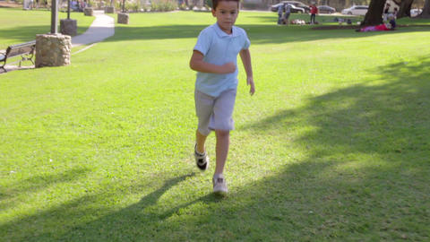 Young Boy Playing Football In Park stock footage