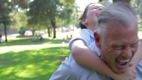 Grandfather Giving Grandson Piggyback Ride Through Footage