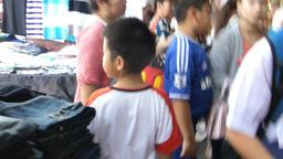 A boy navigating between stalls in narrow aisles o Footage