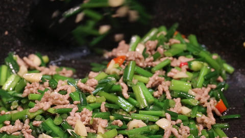 Woman cooking chive bud and ground pork Live Action