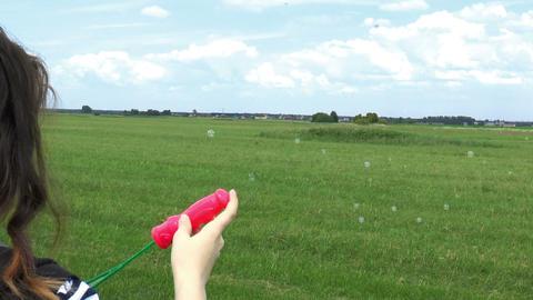 Beautiful Woman Blowing Soap Bubbles on Grass Fiel Footage