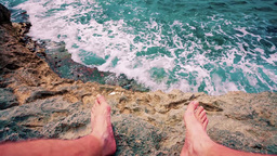 feet on a rock and sea Live Action