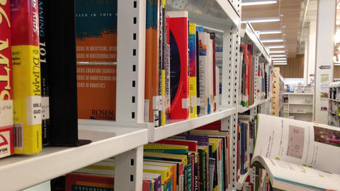 Female student taking book from shelf in library Footage