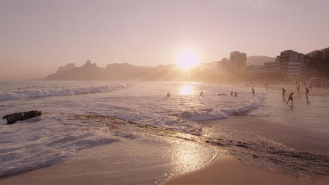 Shot of the sun about to set with people on the beach in Rio, Brazil Footage