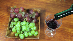 Pouring Red Wine Into A Glass. Grapes Footage