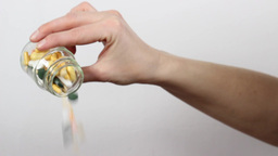 Hand Throwing Out Medicines Out Of The Bottle stock footage