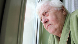 Elderly woman looking through the window 2 Footage