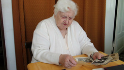 Elderly Woman Is Watching Her Family Old Photos 2 stock footage